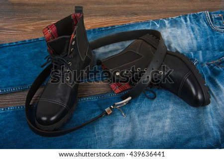 Black men's shoes, jeans and a belt on the wooden background