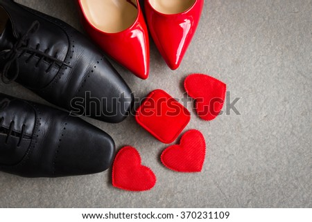 Black men shoes and red women shoes with red heart on gray background - stock photo