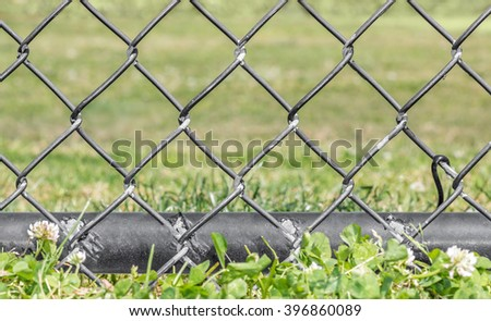 Black metal chainlink fence bottom pole in clover and grass, low angle view. Selective focus on worn fence, close up detail.  - stock photo
