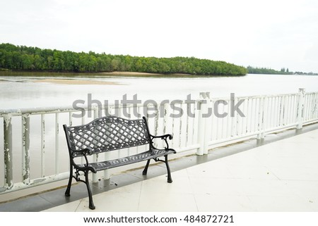 Black metal chair on the floor and white fence near the sea with mangrove forest in the evening.