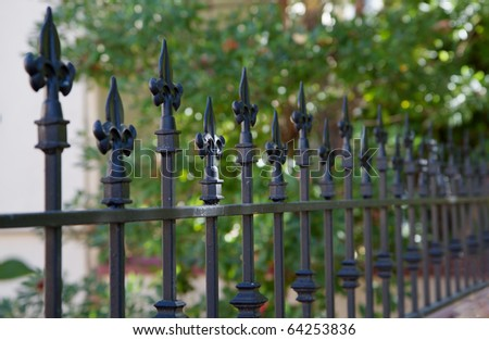 Black metal spiked residential fence diminishing to soft focus in the distance - stock photo