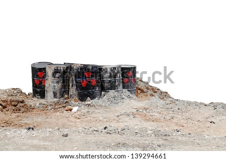 Black metal storage drums with radioactive symbol buried on a dilapidated waste storage site, isolated against white for the concept of dangerous toxic waste. - stock photo
