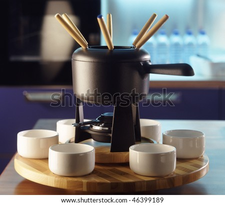 black metallic swiss fondue on the wooden table in the kitchen - stock photo