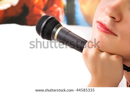 Black microphone in a hand on a white background