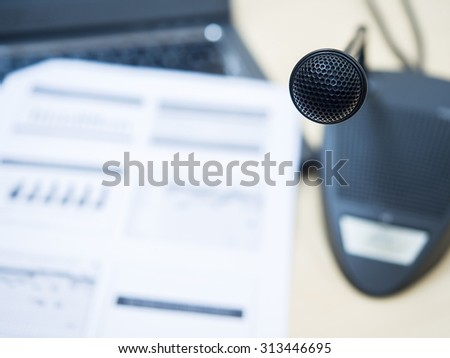 Black microphone in conference room or symposium event with de focused laptop and document sheet. - stock photo