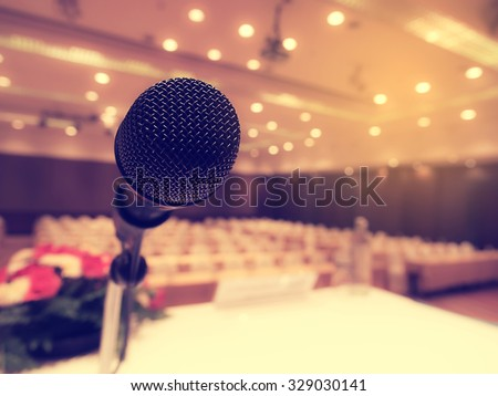 Black microphone in  empty conference room or concert hall  with defocused bokeh lights in background. Extremely shallow dof.  : Vintage style and  filtered process. - stock photo