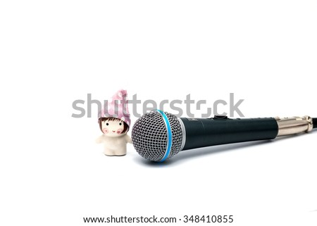 Black microphone isolated on white with lovely girl doll - stock photo