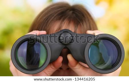 Black modern binoculars in hands on green background - stock photo
