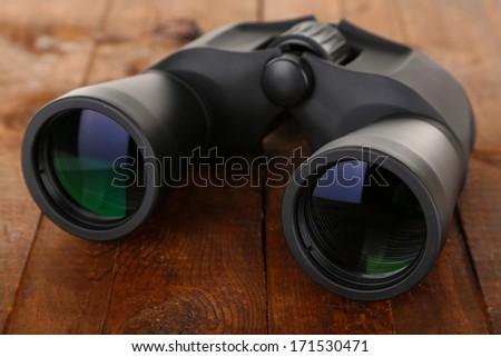 Black modern binoculars on wooden background - stock photo