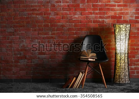 Black modern chair with lamp and books on brick wall background - stock photo