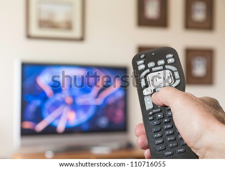 Black modern TV remote control being pressed by thumb with out of focus screen background - stock photo