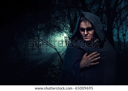 Black monk in the night mystery forest. - stock photo