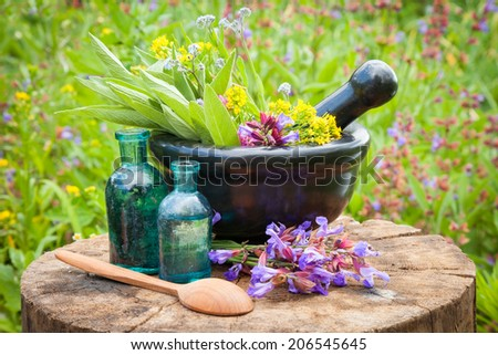 black mortar with healing herbs and sage, glass bottle of essential oil outdoors - stock photo