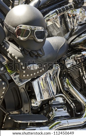 Black motorcycles with black leather seats and helmet and chrome parts - stock photo