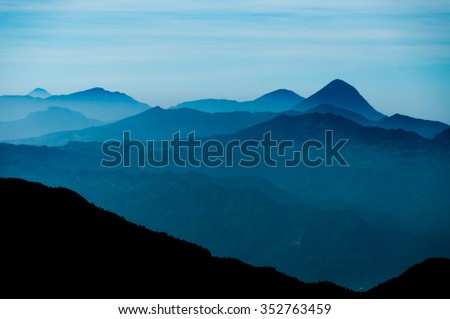 Black Mountain Silhouette in front of Skyscape cold blue mountains with mist and fog close to Quetzaltenango in Guatemala - stock photo