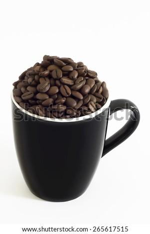 Black mug filled of coffee beans - stock photo