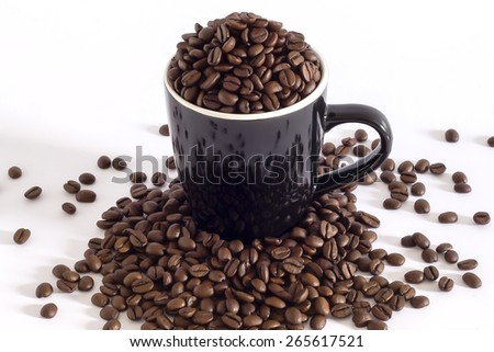 Black mug filled of coffee beans and some more over the table - stock photo