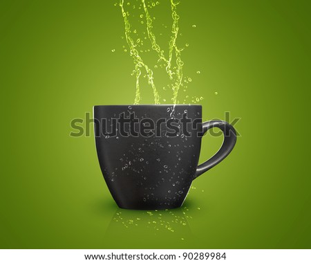 black mug with water splash on green background. - stock photo
