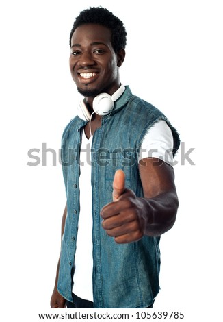 Black music lover showing thumbs up to camera - stock photo