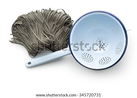 black noodles with squid sepia ink and colander on white background - stock photo