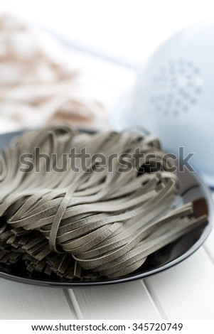 black noodles with squid sepia ink on black plate - stock photo