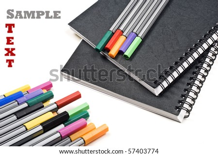 Black note books and colorful pens on a white background with space for text - stock photo