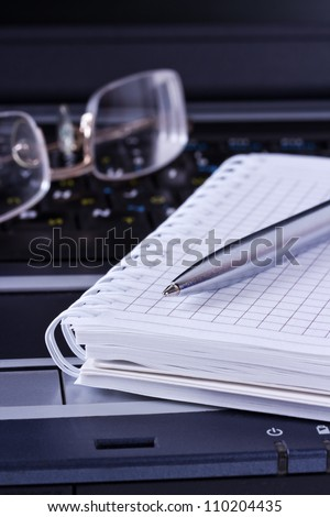 Black notebook with glasses and notepad and pen on it - stock photo