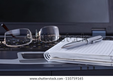 Black notebook with notepad pen and glasses lying on it - stock photo