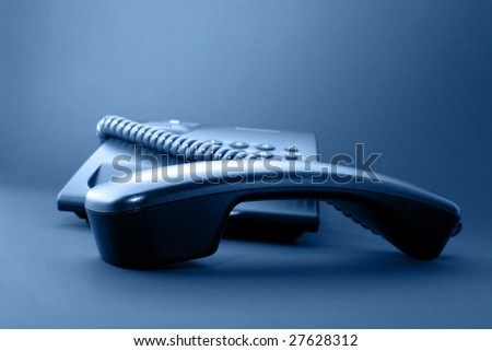 Black office phone and handset isolated on black background and blue toned - stock photo