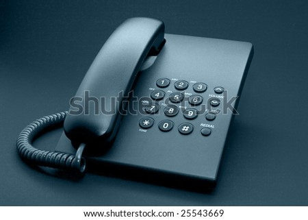 Black office phone with cord isolated on black background - stock photo