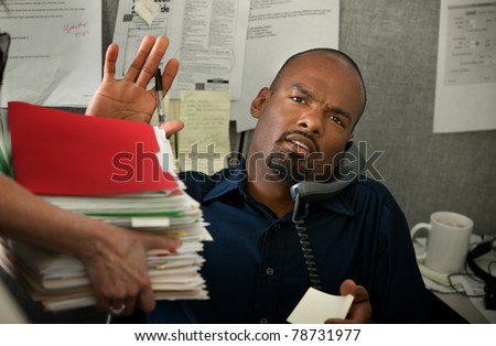 Black office worker with heavy workload on a phone call - stock photo