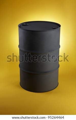 Black oil drum shot on bright yellow background with space for copy