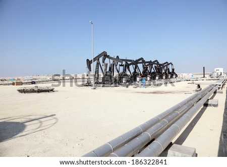 Black oil pump jacks in the desert of Bahrain, Middle East - stock photo