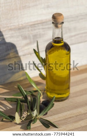 Black olives and a bottle with natural olive oil on a sunny day on a wooden background