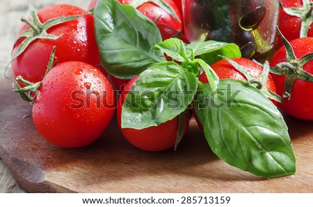 Black olives, fresh green basil and ripe red tomatoes on old wooden table, selective focus - stock photo
