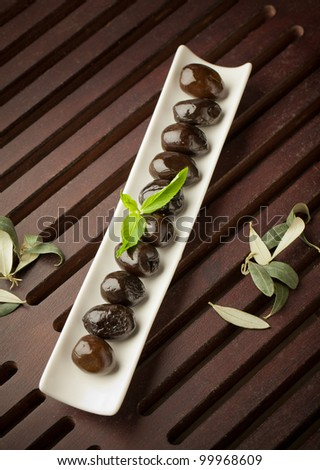 Black olives in a plate on wooden table - stock photo