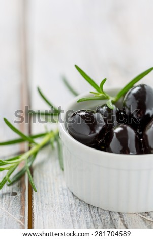 Black olives in a small white bowl on a rustic wooden table with rosemary - stock photo