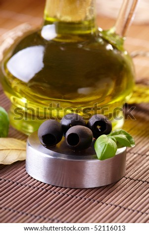 Black olives with fresh basil and oil in background