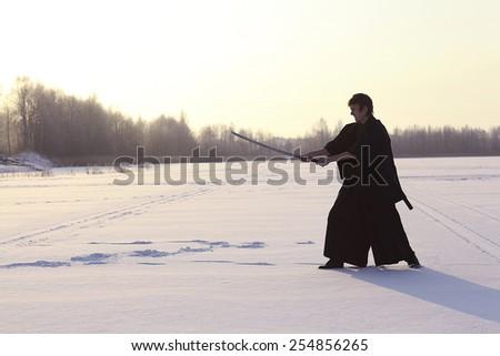 Black oriental martial arts warrior winter training - stock photo
