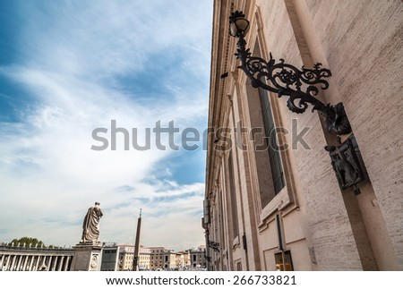 Black ornate lantern on the wall. Statue of the Saint Peter and egyptian obelisk at background. Vatican City, Rome, Italy - stock photo