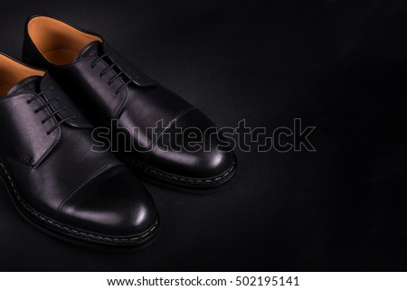 Black oxford shoes on black background. Back view. Copy space.