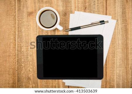 Black pad screen on wooden table with coffee, paper sheets and pen. Topview, Mock up