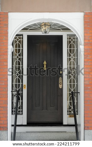 Black Paneled Front Door with Ornate Framing Windows under White Arch - stock photo