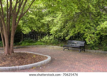 Black park bench on red brick - stock photo