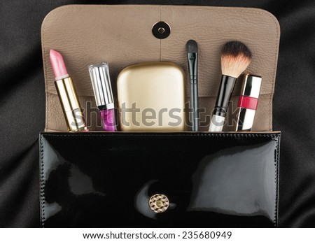 Black patent leather bag  with cosmetics, on black background - stock photo