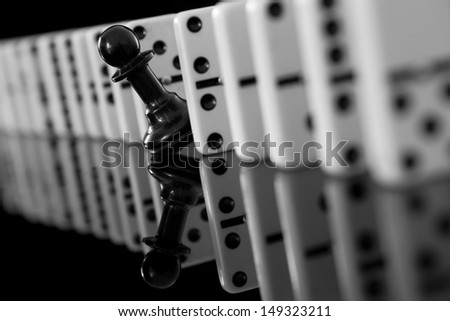 black pawn among domino pieces - stock photo