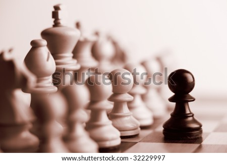 Black pawn and white chess pieces sepia tone - stock photo