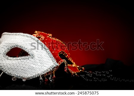 Black peal near white and red carnival masks - stock photo
