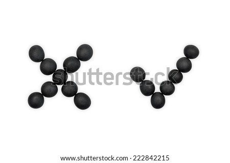 Black pebble cross and check marks isolated on white - stock photo