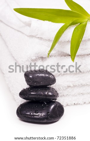 Black pebbles drops of water and towels. - stock photo